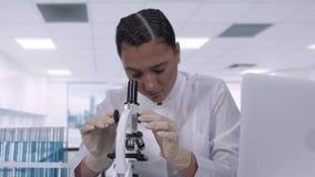 Een zitting van de microbioloogvrouw bij een lijst in een chemisch laboratorium bekijkt biologische monsters onder een microscoop stock video