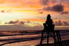 Een zitting van de silhouetvrouw op een badmeestertoren die van de zonsopgang op een strand en de zon` s stralen genieten die de  stock foto's