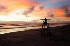Een zitting van de silhouetvrouw op een badmeestertoren met open wapens die van de zonsopgang op een strand en de zon` s stralen  stock afbeelding