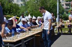 Een zitting van een gelijktijdig spel van een grandmaster met eenvoudige schaakspelers stock foto's
