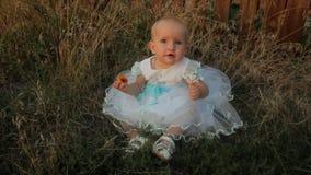 Een zitting van het babymeisje in het hoge gras in een witte kleding, etend een abrikoos en het begin scheuren gras dichtbij haar stock footage