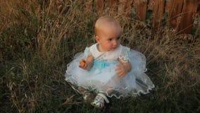 Een zitting van het babymeisje in het hoge gras in een witte kleding, etend een abrikoos, glimlachend en slingerend haar benen Zo stock video