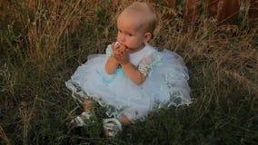 Een zitting van het babymeisje in het hoge gras in een witte kleding Zij knaagt aan een abrikoos en kijkt rond Zonsondergang in d stock videobeelden