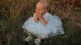 Een zitting van het babymeisje in het hoge gras in een witte kleding Zij knaagt aan een abrikoos Zonsondergang in de zomer stock video