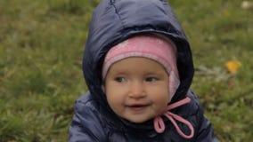Een zitting van het babymeisje op een gazon, het glimlachen en het slingeren stock videobeelden