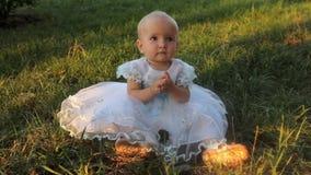 Een zitting van het babymeisje op het gras in een witte kleding en het slaan van haar handen Zonsondergang in de zomer stock videobeelden