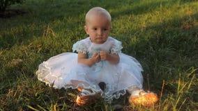 Een zitting van het babymeisje op het gras in een witte kleding, onderzoekend de camera en ziet dan weg eruit Zonsondergang in de stock footage