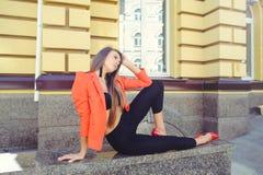 Een zoet gezicht is een geheim Het manierportret van een gelukkige vrouw in rood stijljasje en zwarte broek zit op de achtergrond Stock Foto