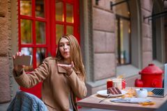 Een zoet jong meisje, zittend in een koffie, makend selfie op een mobiele telefoon en verzendend een luchtkus Royalty-vrije Stock Foto