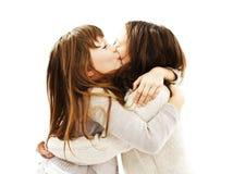 Een zoet meisje die haar oudere zuster kussen stock fotografie