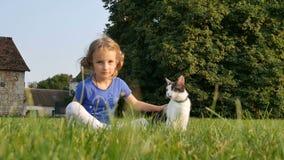 Een zoet meisje en een drie-gekleurde kat zitten in het gras naast elkaar Tegen de achtergrond van een oud huis en lang stock video