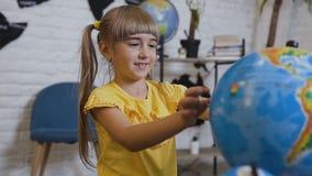 Een zoet meisje in een gele T-shirt zit bij de lijst in het klaslokaal van aardrijkskunde en merkwaardig bestudeert de bol of stock video