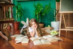 Een zoet schoolmeisje van ondergeschikte klassen met lang blond haar met boeken, een schoolraad en appelen stock afbeelding