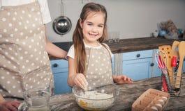 Een zoete dochter mengt eieren en bloem in een kom Het meisje gaat mafina met haar moeder doen stock afbeeldingen