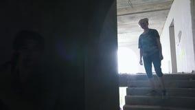 Een zombie op de treden lopen en een mensenoverlevende die met een kanon in hen streven stock videobeelden