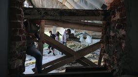 Een zombieaanval in de verlaten bouw Overlevenden die van de zombieën ontsnappen en een omheining van hen plaatsen stock footage