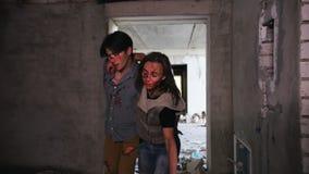 Een zombieaanval in de verlaten bouw Vermoeide overlevenden die door elkaar houden en van de zombieën in daglicht ontsnappen stock footage