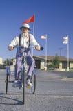 Een zonderlinge bejaarde die een driewieler berijdt Stock Foto's
