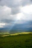 Een zonnestraal die de aarde op een regenachtige dag toenemen stock foto