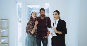 In een zonnig de agentenhuis die van de dag aantrekkelijk vrouw het moderne huis vertegenwoordigen aan een nieuw charismatisch pa stock video