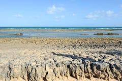 Een zonnig strand met lagen van water Stock Afbeeldingen