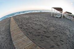 Een zonsopgang op een overzees zandstrand Er zijn heel wat voetafdrukken stock foto