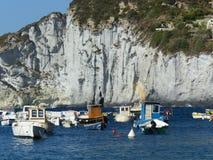 Een zuivere klippen witte rotsen met in de voorgrondkleine boten op het overzees aan Ponza in Italië Royalty-vrije Stock Foto's