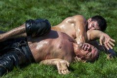 Een zwaargewicht worstelaar wordt gespeld aan het gras bij het de Olie van Elmali Turkse het Worstelen Festival in Elmali in Turk stock fotografie