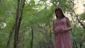 Een zwanger meisje bevindt zich in het park Een meisje in een gestreepte wit-rode kleding bevindt zich en houdt haar hand op haar stock video