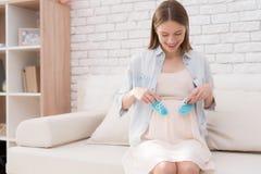 Een zwanger meisje houdt schoenen voor pasgeboren Stock Afbeelding