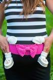 Een zwanger meisje in een kleding, die op een jongen wachten, overhandigt op een zwangere buik, wachtend op dit, steun van ouders royalty-vrije stock afbeelding