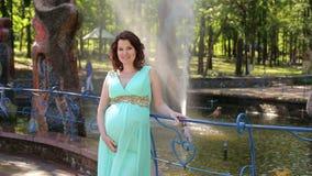 Een zwanger meisje in een lange kleding bevindt zich in een stadspark op een fonteinachtergrond stock footage