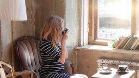 Een zwangere blonde vrouw in een koffie het drinken thee door het venster, die op de leunstoel zitten Mooi verspreid licht Beeld  stock footage