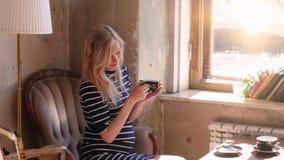 Een zwangere blonde vrouw in een koffie het drinken thee door het venster, die op de leunstoel zitten mooi verspreid licht Beeld  stock videobeelden