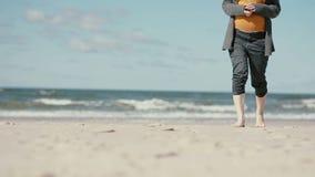 Een zwangere donker-haired jonge vrouw loopt blootvoets langs een zandig strand die langzaam de camera naderen stock footage