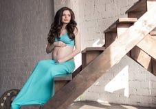Een zwangere jonge vrouw in een blauwe rok en een bovenkant zit op de stappen van een houten trap stock afbeelding