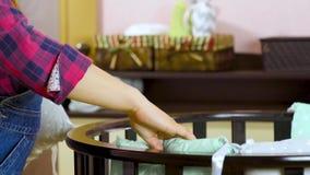 Een zwangere vrouw als voorbereiding op een pasgeboren kind wordt voorbereid op de vergadering Het vouwen van het houten meubilai stock videobeelden