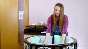 Een zwangere vrouw als voorbereiding op een pasgeboren kind wordt voorbereid op de vergadering Het vouwen van het houten meubilai stock footage
