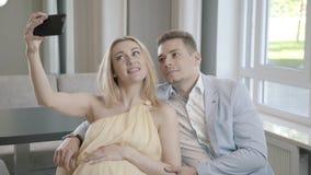 Een zwangere vrouw en haar echtgenoot in een licht kostuum worden gefotografeerd stock videobeelden