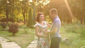 Een zwangere vrouw en haar echtgenoot lopen in het Park stock footage