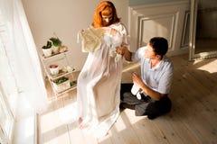 Een zwangere vrouw en haar echtgenoot zitten dichtbij een venster en bekijken kleren voor pasgeboren royalty-vrije stock foto