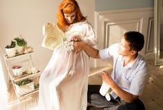 Een zwangere vrouw en haar echtgenoot zitten dichtbij een venster en bekijken kleren voor pasgeboren stock fotografie