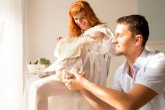 Een zwangere vrouw en haar echtgenoot zitten dichtbij een venster en bekijken kleren voor pasgeboren stock foto