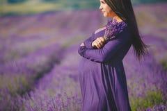 Een zwangere vrouw geniet van de kleurenlavendel Royalty-vrije Stock Afbeeldingen