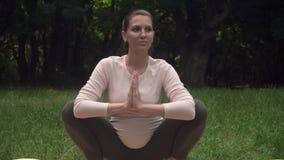 Een zwangere vrouw het praktizeren yoga in het park op een deken, die asana Malasana doen, stelt van een kraai of stel van een ki stock videobeelden