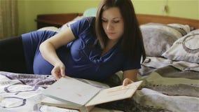 Een zwangere vrouw met een grote buik met een fotoalbum in haar handen stock footage
