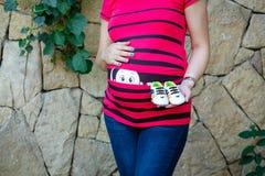 Een zwangere vrouw in een rode gestreepte blouse hield in de handen van kindschoenen op de achtergrond van een steenmuur en groen royalty-vrije stock foto's