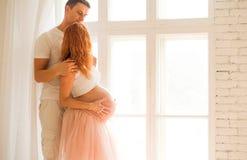 Een zwangere vrouw in een witte bovenkant en een smoking begrenzen en haar echtgenoottribune dichtbij een groot venster en geniet royalty-vrije stock afbeeldingen