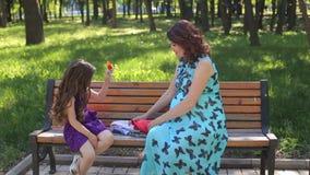 Een zwangere vrouw zit met haar dochter op een een parkbank en spel stock videobeelden