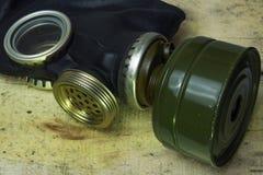 Een zwart gasmasker met een membraan voor het spreken ligt op houten raad Een militair concept is een chemische of radioactieve a Stock Afbeeldingen